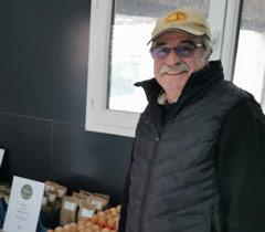 Dany avec son miel bio et ses oeufs de poules frais lors du marché fermier